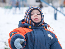 Attractive baby boy playing with the first snow. He smiles and looks snowman. Thick blue-orange jumpsuit bright striped. Attractive baby boy playing with the Stock Image
