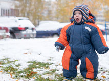 Attractive baby boy playing with the first snow. He smiles and looks snowman. Thick blue-orange jumpsuit bright striped Stock Photos
