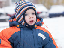 Attractive baby boy playing with the first snow. He smiles and looks snowman. Thick blue-orange jumpsuit bright striped. Attractive baby boy playing with the Royalty Free Stock Photos