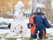 Attractive baby boy playing with the first snow. He smiles and looks snowman. Thick blue-orange jumpsuit bright striped Royalty Free Stock Photo