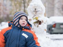 Attractive baby boy playing with the first snow. He smiles and looks snowman. Thick blue-orange jumpsuit bright striped Royalty Free Stock Image