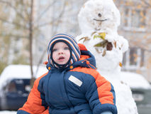 Attractive baby boy playing with the first snow. He smiles and looks snowman. Thick blue-orange jumpsuit bright striped Stock Images