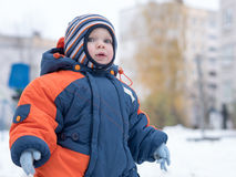 Attractive baby boy playing with the first snow. He smiles and looks snowman. Thick blue-orange jumpsuit bright striped Stock Photo