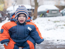 Attractive baby boy playing with the first snow. He smiles and looks snowman. Thick blue-orange jumpsuit bright striped Stock Photography