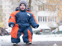 Attractive baby boy playing with the first snow. He smiles and looks snowman. Thick blue-orange jumpsuit bright striped Royalty Free Stock Images
