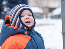 Attractive baby boy playing with the first snow. He smiles and looks snowman. Thick blue-orange jumpsuit bright striped Royalty Free Stock Photos