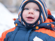 Attractive baby boy playing with the first snow. He smiles and looks snowman. Thick blue-orange jumpsuit bright striped Royalty Free Stock Photography
