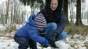 Attractive baby playing with mother in the winter outside in the woods. Mother molds for snowballs year-old boy.  stock footage