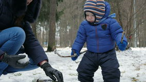 Attractive baby playing with mother in the winter outside in the woods. Mother molds for snowballs year-old boy.  stock video footage