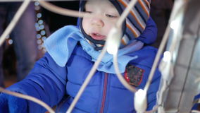 Attractive baby treats a garland in the town square at the Christmas tree. He mittens touches bulbs stock footage