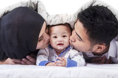 Attractive baby under blanket with parents Stock Images