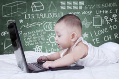 Attractive baby using laptop with scribble background Royalty Free Stock Photo
