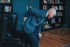 The attractive bald bearded man holding onto his back, trying to get up from his leather chair. Rich people cry too. The attractive bald bearded man is holding stock photos