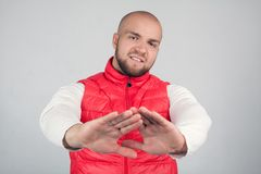 Attractive bald male shows refusal gesture, doesnt want to participate in meeting, says it is not for me, leave me in piece, has stock photography