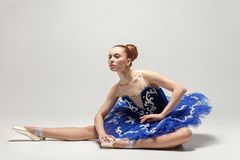 Attractive ballerina with bun collected hair wearing blue dress royalty free stock photo