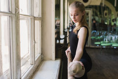 Attractive ballerina warming up in ballet class Stock Photography