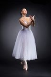 Attractive ballet dancer standing and smiling. Royalty Free Stock Images