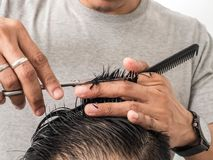 Attractive barber with dark hair doing a haircut for client with scissors isolated on white background.  royalty free stock images