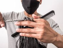 Attractive barber with dark hair doing a haircut for client with scissors isolated on white background.  stock photography