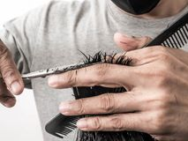 Attractive barber with dark hair doing a haircut for client with scissors isolated on white background.  stock image