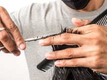 Attractive barber with dark hair doing a haircut for client with scissors isolated on white background.  stock photos