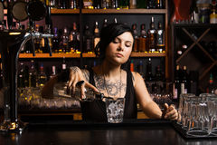 Attractive bartender. Pouring a drink Royalty Free Stock Photo