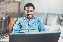 Attractive bearded African man using laptop while relaxing on armchair in modern office.Concept of young business people Stock Photography