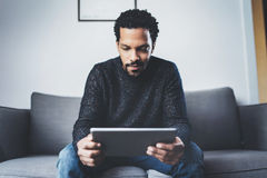 Attractive bearded African man using tablet while sitting on sofa in his modern office.Concept of young business people. Selective focus.Attractive bearded Royalty Free Stock Photography