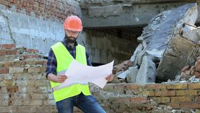 Attractive bearded builder in orange helmet on destroyed building background. Serious builder analysing drawing. And looking on both sides. Preparation for stock footage