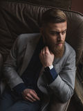 Attractive bearded businessman is deciding serious question. Cheerful young man is making decision. He is sitting in chair and touching his beard pensively Stock Photos