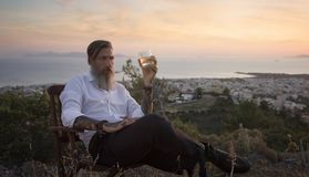 Attractive bearded businessman is sitting on the chair on the mountain and drinking whiskey at sunset.  stock photography