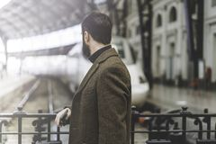 Attractive bearded businessman standing at the hall of railway station and waiting his train.Visual effects. Royalty Free Stock Photo