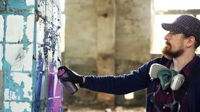 Attractive bearded guy is holding aerosol paint and drawing graffiti on pillar inside spacious abandoned house. Creative. Young people, empty buildings and stock footage