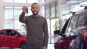 Guy holds car key in his hand. Attractive bearded guy holding car key in his hand. Handsome african american man standing near new crossover at the showroom Stock Photo