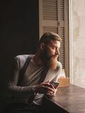 Attractive bearded guy is messaging on telephone. Portrait of handsome young man using a mobile phone. He is sitting near the window and looking sideways Royalty Free Stock Photos