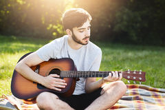Attractive bearded male guitarist wearing casual clothes sitting crossed legs with guitar liking his hobby while being at green me. Adow or field. Romantic man Stock Images