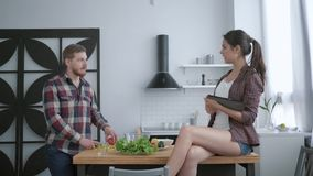 Attractive bearded male prepares delicious healthy salad from fresh vegetables and greens and female sits on table with. Tablet in hand and talks in kitchen stock video footage
