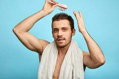 Attractive bearded man combing his wet hair royalty free stock images