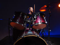 Attractive bearded man drummer sitting and playing on his kit Royalty Free Stock Photo