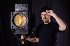 Attractive bearded man hand on the cap near stage spotlight Stock Photo
