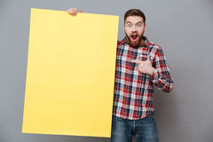 Attractive bearded man holding copyspace board and pointing. Photo of attractive bearded man holding copyspace board and pointing standing over grey background Stock Photos