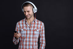 Attractive bearded man holding phone. Enjoy the music. Delighted male person listening music with headphones holding in his right hand the phone choosing the Stock Photo