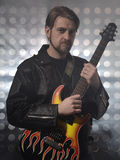 Attractive bearded man  plays guitar in smoke Stock Images