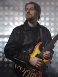 Attractive bearded man  plays guitar in smoke Royalty Free Stock Photos