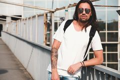 Attractive bearded man portrait with sunglasses. Young attractive bearded man with tattoos and long hair wearing sunglasses, white shirt and backpack posing on Royalty Free Stock Image