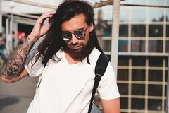 Attractive bearded man portrait with sunglasses. Young attractive bearded man with tattoos and long hair wearing sunglasses, white shirt and backpack posing on Royalty Free Stock Photos