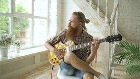 Attractive bearded man sitting on chair learning to play guitar in modern bedroom at home. Attractive bearded man sit on chair learning to play guitar in modern stock video