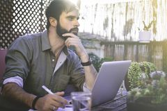 Attractive Bearded Man sitting at vintage natural rough wood desk working on laptop computer at cafe terrace surrounded. Green flores and cactus.Out of office royalty free stock photography