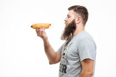 Attractive bearded man standing and holding hot dog Royalty Free Stock Images