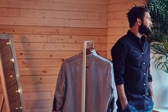 A man fit on fashionable shirts. Attractive bearded tattooed male fit on fashionable shirts in a store changing room Stock Photo